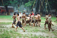 Boys playing football in rain
