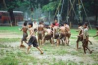 Boys playing football in rain
