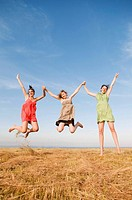 Three girls jump and hold hands up high