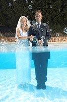 Bride and groom in pool with bubbles