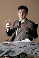 Businessman sitting at a desk covered in newspapers