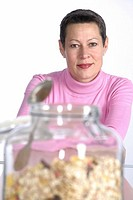 Woman at table with cereal jar