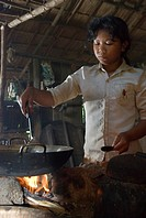 Young woman cooking on open fire in a traditional kitchen, Koh Kong Province, Cambodia