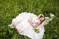 Woman in white dress lying down in meadow with wildflowers