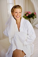 Smiling woman drying her hair with a towel