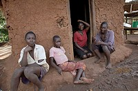 Young teens sitting outside kitchen, Bugiri village, Kayunga District, Uganda