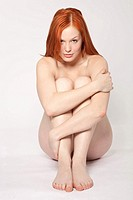 Young redhaired woman sitting nude