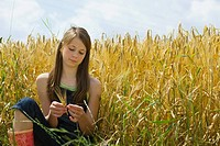 A girl sitting in a corn field