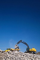 Excavator on piles of rubble