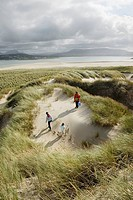 Family is hiking in dunes at the northern coast of Co Donegal, Ireland