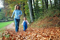 Mother with daughter running on path full of leaves in fall, having fun and laughing, autumn foliage covering path in forest, autumn, fall, Zuerich, S...