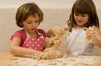 Close_up of two girls kneading flour