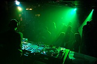 Club DJ playing a set in a crowded nightclub