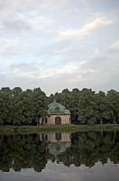 The waters of Nymphenburg canal reflekting a historical building and some trees, Munich, Bavaria, Germany