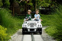 Two children are driving with a little car in theme park Legoland, Guenzburg, Germany