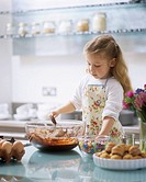 A young girl baking cakes