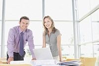Businesspeople leaning on desk smiling