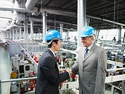 Businessmen in hard_hats shaking hands