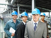 Businesspeople wearing hard_hats in warehouse