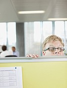 Businessman peering over cubicle wall