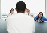 Businesspeople laughing during meeting in conference room
