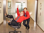 Businessman pushing co_worker in chair in corridor