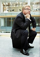 Businessman sitting on briefcase