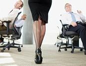 Businessmen watching sexy co_worker