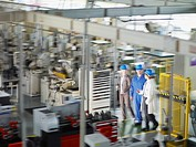 Businesspeople in hard_hats walking on factory floor