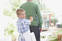 Boy tying man's apron in backyard