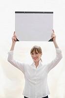 Woman holding desk blotter over head