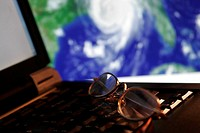 Tracking A Hurricane portrayed by eyeglasses atop a laptop computer