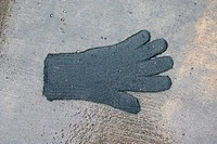 Lost glove on wet sidewalk