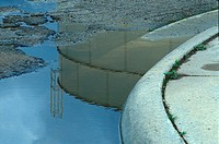 Water Tower Reflection In Curbside Puddle
