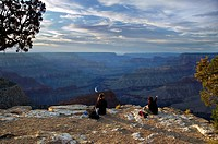 Two hikers at days end surveying the Grand Canyon