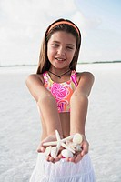 Girl on beach holding delicate starfish and shells