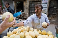 Delhi, India, Man buying fruit from market stall