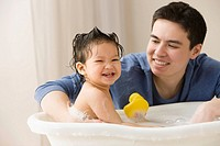 Mixed race father washing his daughter in bathtub