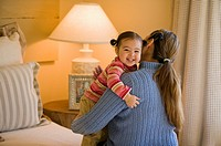 Hispanic mother and daughter hugging in bedroom