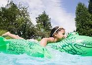 Hispanic girl playing in swimming pool