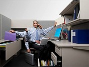 Businessman multi_tasking in cubicle with extra arms
