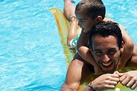 Father giving son piggyback ride in swimming pool