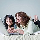 Young woman and mother using laptop on bed