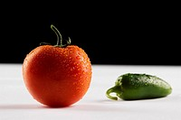 Close_up of a tomato and a green chili pepper