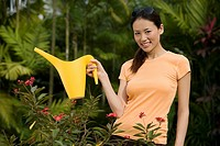 Portrait of a young woman watering plant with a watering can and smiling
