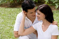 Close_up of a young couple sitting in a garden and smiling