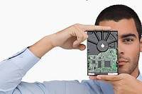 Portrait of a businessman holding a hard drive in front of his face