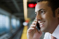 Close-up of a businessman talking on a mobile phone at a subway station (thumbnail)