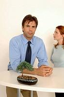 Business man and woman staring at bonsai trees.