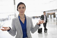 Businesswoman talking on a hands free device at an airport lounge (thumbnail)